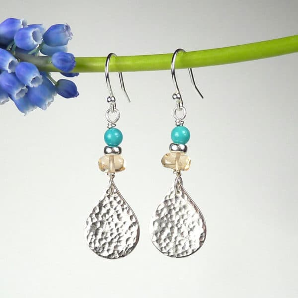 Hammered silver drop earrings with gemstones.